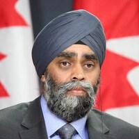 Le ministre Sajjan devant des drapeaux canadiens.