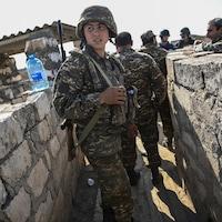 Un homme en treillis militaire dans une tranchée bordée de murets en pierres.