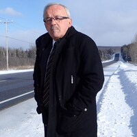 Le maire de la municipalité de Lac-aux-Écorces dans les Hautes-Laurentides, et président du Comité S.O.S 117, Pierre Flamand. Il pose en bordure de la route près d'un panneau électronique sur lequel est écrit: conditions routières changeantes.