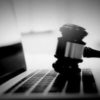 Un maillet de juge sur le clavier d'un ordinateur portable.