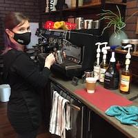 Une femme fait du café.