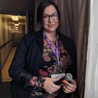 Heather Abbey, qui regarde la photographe, debout dans le corridor d'un hôtel.
