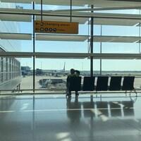 Un homme est assis sur un siège dans un terminal de l'aéroport.