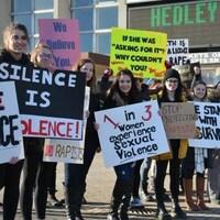 Des manifestants qui tiennent des pancartes.