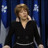 Hélène David devant un micro et des drapeaux du Québec