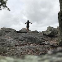Une femme court sur des grosses roches.