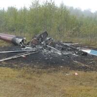 Un hélicoptère incendié près d'une forêt.