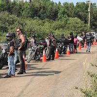 Des motards patientent sur le bas-côté d'une route en gravier.
