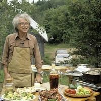 À l'extérieur, le chef Henri Bernard est debout, souriant, devant une table recouverte de plats de salades, brochettes et piments.