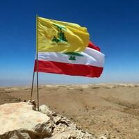 Le drapeau du Liban et celui du Hezbollah flottant au-dessus d'une vallée désertique dans la ville d'Ersal, dans le nord du Liban.