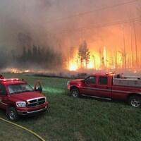 Deux véhicules de pompiers sont stationnés dans un champ. En arrière-plan, des arbres flambent.
