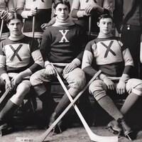 Photo en noir et blanc de cinq joueurs de hockey qui posent avec leur bâton à la main.