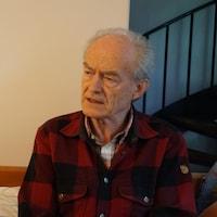 Jean Meyer est assis sur son divan.