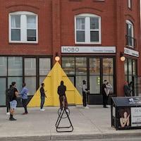 Des clients qui font la file à l'extérieur du magasin de cannabis.