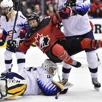 L'attaquante du Canada Ann-Sophie Bettez est repoussé par la gardienne des États-Unis Katie Burt après que le Canada eut marqué lors de la première période du match de la série de rivalité à Toronto le jeudi 14 février 2019.