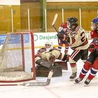 Des joueurs d'équipe adverses devant la cage d'un gardien de but sur une patinoire.
