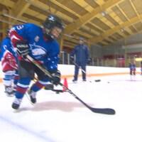Des jeunes jouent au hockey sur une patinoire intérieure.