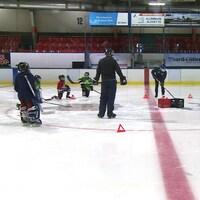 De jeunes joueurs de hockey s'exercent sur la glace.