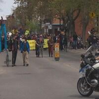 Des citoyens défilent dans la rue avec un policier à moto devant.