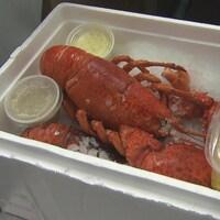 Un homard repose dans une boîte avec divers accompagnements.