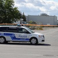 Un véhicule de police est garé à l'extérieur du périmètre de sécurité.