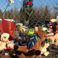 Des fleurs et des peluches déposées par le public au pied d'une clôture grillagée près du lieu où les ossements de Cédrika Provencher ont été retrouvés en décembre 2015.