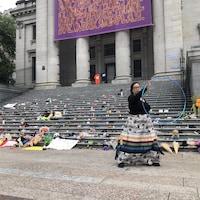 Une femme avec un cerceau devant les marches de la Vancouver Art Gallery où des centaines de chaussures sont alignées.