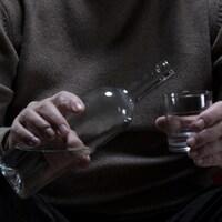 Un homme se verse un verre d'alcool.