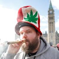 Un homme fume de la marijuana lors du rassemblement sur la colline du Parlement à Ottawa en avril 2018.
