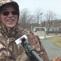 Un homme avec un manteau, un capuchon et des lunettes de soleil répond au micro avec un large sourire.