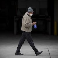 Un homme marche dans la rue à Toronto avec un masque et des gants en regardant sont téléphone cellulaire.