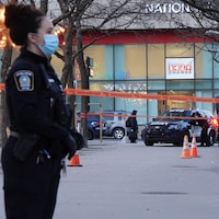 Une policière se tient près d'un ruban de sécurité. Derrière elle, une autopatrouille est stationnée.