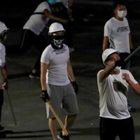 Des hommes en t-shirt portent des masques et des casques.