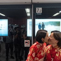 Deux femmes s'embrassent dans une rue de Hong Kong.