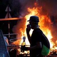 Un manifestant tient un cocktail Molotov alors que des étudiants affrontent la police antiémeute à l'Université chinoise de Hong Kong.