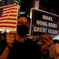 Un homme avec un masque tient un petit drapeau américain et une pancarte où est écrit : « Make Hong Kong great again! »