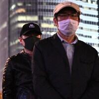 Les manifestants, debout, portent des masques et des pancartes.
