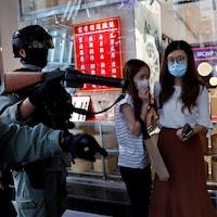Un policier masqué et casqué tient un fusil devant trois jeunes femmes.