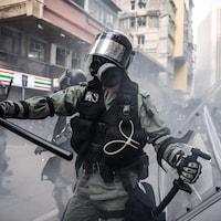 Un policier avec un bâton, et portant des protections
