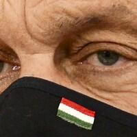 Gros plan des yeux du premier ministre hongrois Viktor Orban. Il porte un masque sur lequel figure le drapeau de la Hongrie.