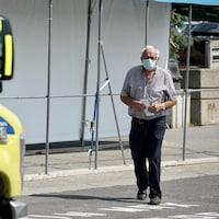 Un homme porte un masque de protection et se dirige vers une ambulance.