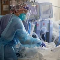Une infirmière se penche sur un patient de la COVID-19 à l'hôpital.