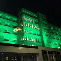 La façade de l'Hôpital d'Alma illuminée en vert.
