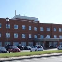 La façade de l'hôpital des Îles-de-la-Madeleine avec des voitures en avant-plan.