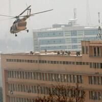 Les forces de sécurité afghanes sont intervenues dans l'hôpital après avoir été déposés sur le toit par un hélicoptère de l'armée. En bas, à gauche, on peut voir des gens ayant trouvé refuge sur le bord d'une fenêtre.