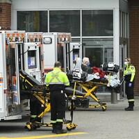 Des ambulanciers devant l'entrée de l'urgence.