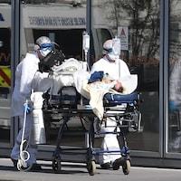 Des infirmiers transportent un patient sous respirateur artificiel.
