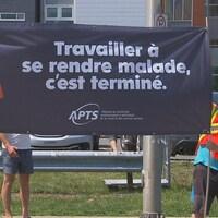 Des gens manifestent avec une pancarte devant l'hôpital à Trois-Rivières.