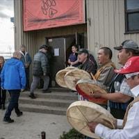 John Horgan entre dans le bâtiment entouré d'Autochtones qui jouent du tambour.