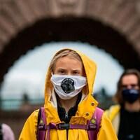 Vêtue d'un imperméable, Greta Thunberg fronce les sourcils. Elle porte un couvre-visage en tissu.